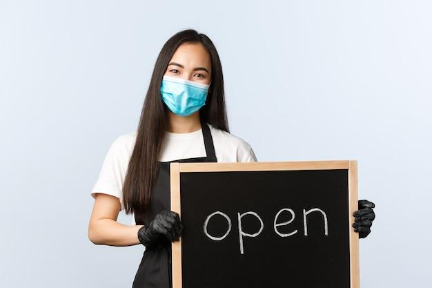 중소기업, covid-19 전염병, 바이러스 및 직원 개념 방지. 웃는 귀여운 아시아 여성 직원, 카페 또는 상점 직원이 열린 사인을 들고 방문자를 초대합니다.