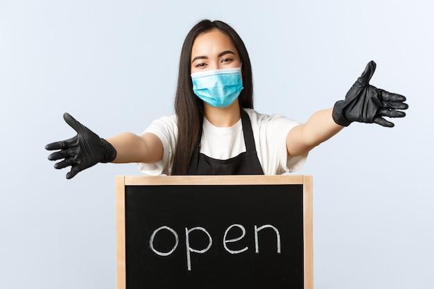 中小企業、covid-19パンデミック、ウイルスと従業員の概念を防ぎます。笑顔のフレンドリーなアジアのカフェワーカー、バリスタが歓迎や挨拶で手を伸ばし、ついに顧客に開放されました。