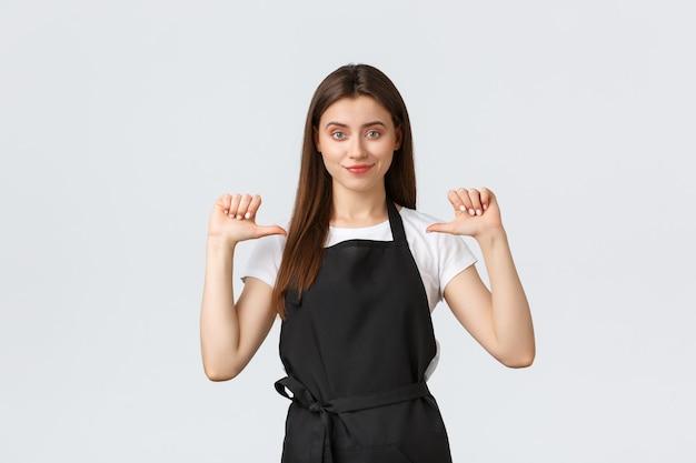 Концепция малого бизнеса, сотрудников и кафе. уверенная в себе красивая женщина-бариста в черном фартуке, указывая на себя и довольная улыбающаяся, дерзкая, лучшая работница месяца.