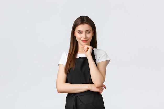 중소기업, 직원 및 커피숍 개념입니다. 자신감이 넘치는 여성 바리스타가 흥미롭게 웃고 있습니다. 아이디어가 있는 사려깊은 판매원에 만족했습니다. 재미있는 계획을 듣고 있는 웨이터.