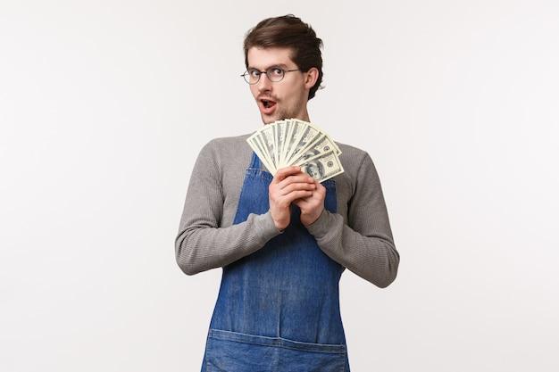 中小企業、金融、キャリアのコンセプト。コーヒーショップでアルバイトをしている熱狂的な若い男性学生は、給料を手にしているエプロン、ドルのファン、お金を稼いでいます。