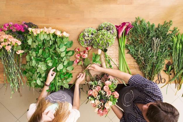 중소기업. 꽃 배달 평면도. 주문을 생성하는 플로리스트, 꽃집에서 장미 꽃다발 만들기.
