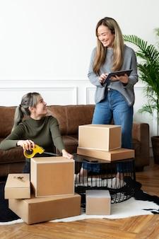 Compagni di amici di piccole imprese che imballano pacchi di prodotti per la consegna