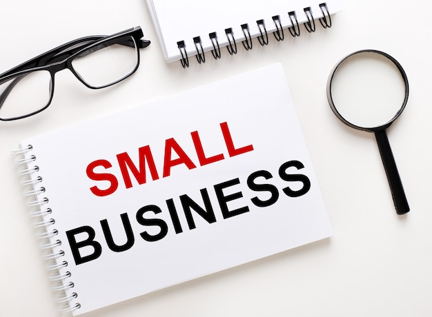 Small business is written in a white notebook on a light surface near the notebook, black-framed glasses and a magnifying glass.