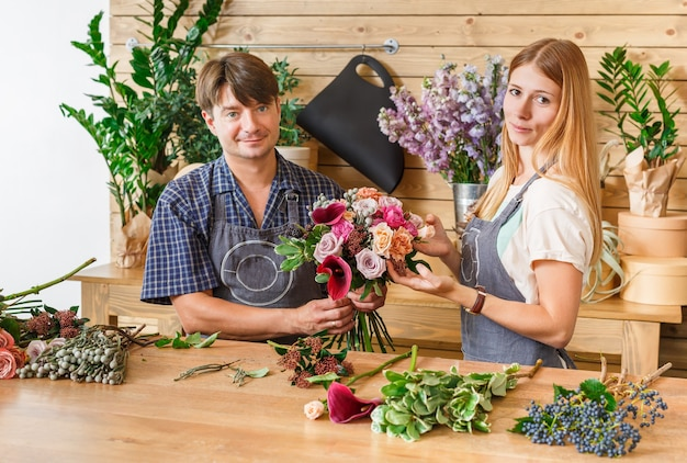 Small business. male and female florists making rose bouquet in flower shop. man owner and woman assistant in floral design studio, making decorations and arrangement. flowers delivery, creating order