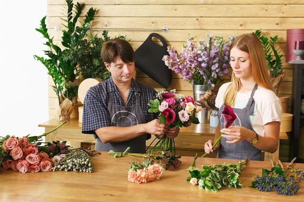 Small business. male and female florists making rose bouquet in flower shop. man owner and woman assistant in floral shop, making decorations and arrangement. flowers delivery, creating order