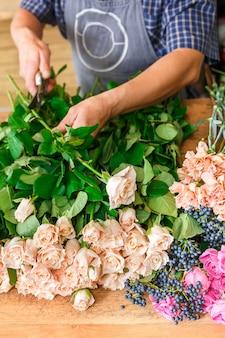 Малый бизнес. мужской флорист вручает крупный план, сокращает розу для букета в цветочном магазине. помощник человека или владелец в студии цветочного дизайна, делая украшения и композиции. доставка цветов, оформление заказа
