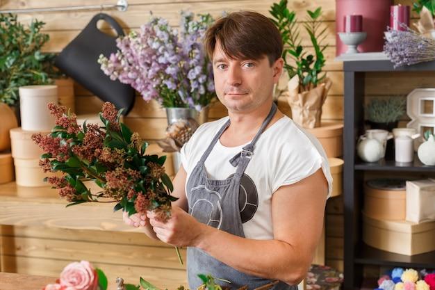 小規模なビジネス。フラワーショップで花束を作る男性の花屋。花のデザインスタジオの男性アシスタントまたはオーナー。装飾やアレンジを行っています。花の配達、注文の作成