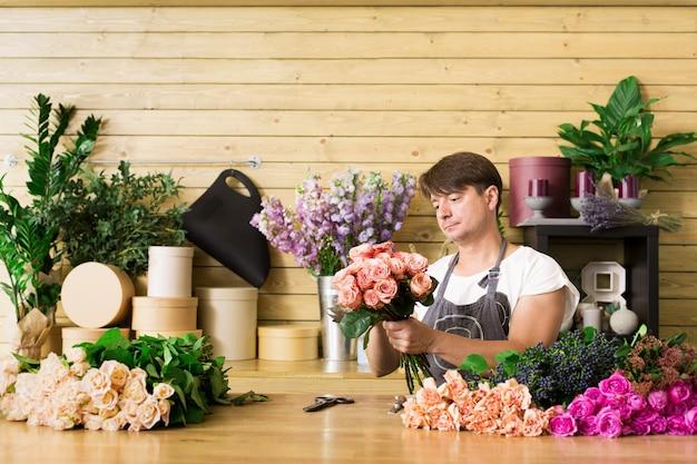 小規模なビジネス。フラワーショップのカウンターデスクでバラの花束を作る男性の花屋。フラワーショップの男性アシスタントまたはオーナー。装飾やアレンジを行っています。花の配達、注文の作成
