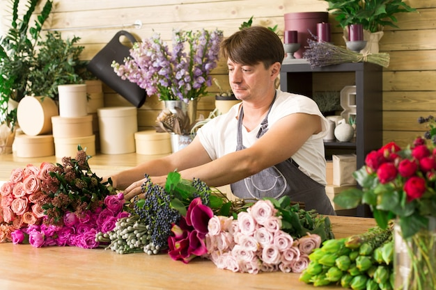Small business. male florist making rose bouquet in flower shop. man assistant or owner in floral shop, making decorations and arrangements. flowers delivery, creating order