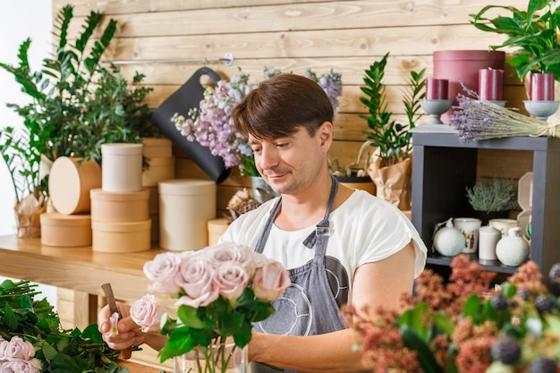 小規模なビジネス。フラワーショップでバラの花束を作る男性の花屋。花のデザインスタジオの男性アシスタントまたはオーナー。装飾やアレンジを行っています。花の配達、注文の作成