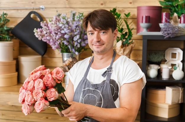 Малый бизнес. мужской флорист делает букет роз в цветочном магазине. помощник человека или владелец в студии цветочного дизайна, делая украшения и композиции. доставка цветов, оформление заказа