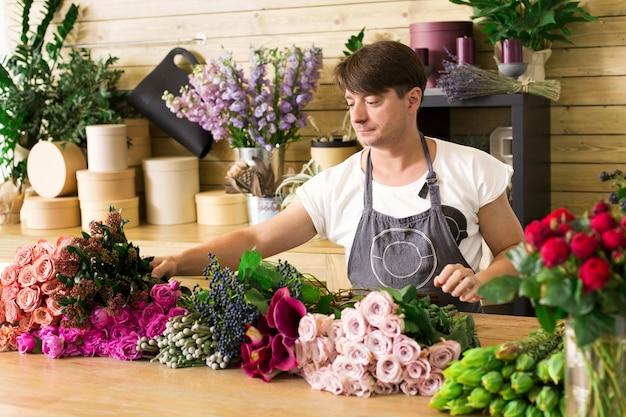小規模なビジネス。フラワーショップでバラの花束を作る男性の花屋。フラワーショップの男性アシスタントまたはオーナー。装飾やアレンジを行っています。花の配達、注文の作成