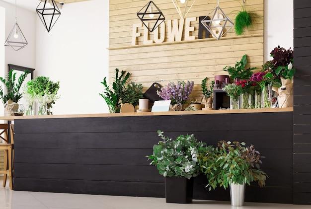小規模なビジネス。モダンなフラワーショップのインテリア。花の配達サービスと鉢、木製のショーケースでの観葉植物の販売。