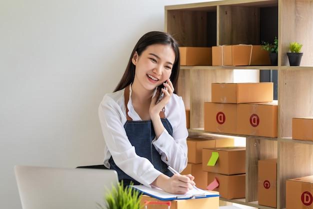 中小企業のオーナーであるアジア人女性は、電話で話すことを楽しんでおり、自宅でメモを取るオンライン販売注文を受け取ります。
