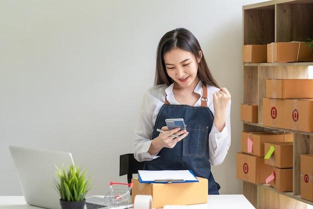 スマートフォンを持っている中小企業経営者のアジア人女性がオンラインノートパソコンの販売に成功し、小包箱が自宅に置かれています。