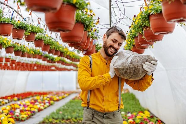 Владелец малого бизнеса несет удобрения на плече во время прогулки в теплице