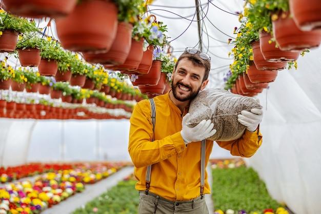 温室の中を歩きながら肩に肥料を運ぶ中小企業の所有者。