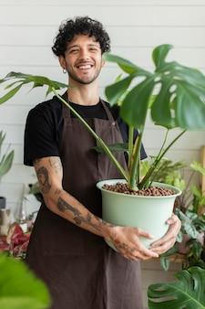 Владелец малого бизнеса держит горшечное растение в магазине