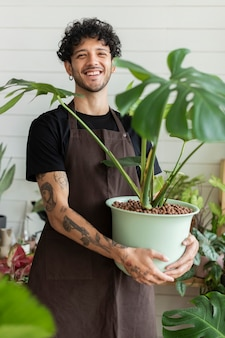 Small business owner holding a potted plant at the shop
