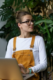 소규모 비즈니스 소유자 또는 프리랜서 정원사 소녀는 원격으로 노트북을 사용하여 클라이언트와 통신합니다.