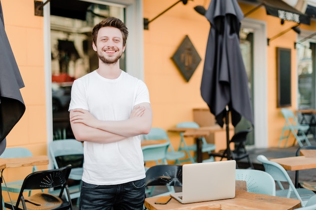 Small business owner outside his cafe with laptop