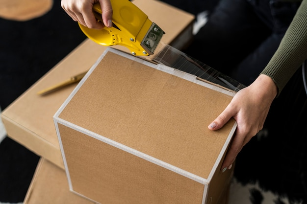 Small business owner packing product parcel boxes for delivery