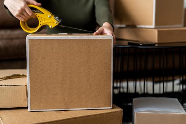 Piccolo imprenditore che imballa scatole per pacchi di prodotti per la consegna