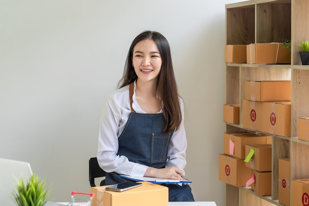 中小企業の所有者は、自宅で小包ボックスを使用してオンラインで販売して幸せなアジアの女性を笑っています。