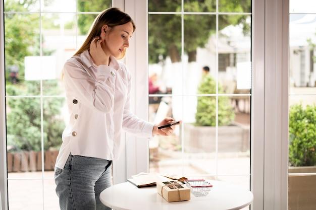 소상공인이 테이블 위 카페에서 제품 사진을 찍고 있다. 전화를 가진 여자의 측면 보기입니다. 판매자 기업가는 온라인 상점을 위해 제품 사진을 찍습니다.