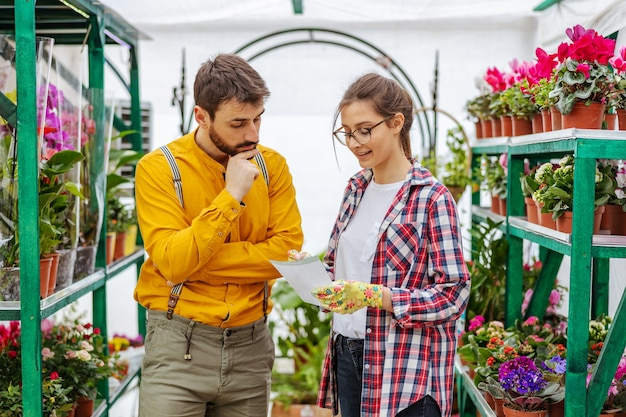 Small business owner taking order from a customer. man standing next to woman and telling her what he want. greenhouse interior.