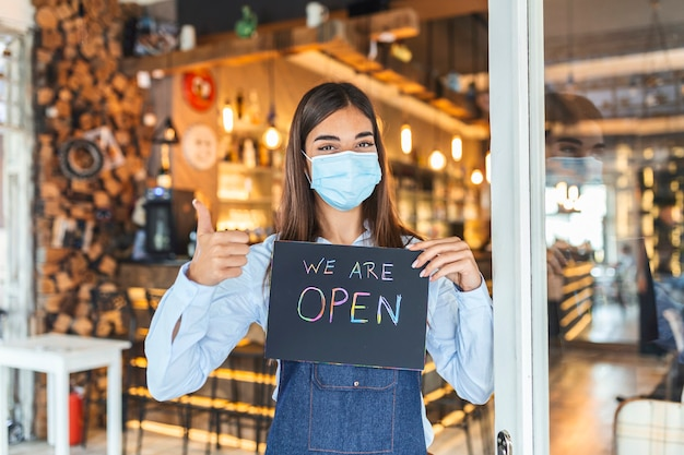 Covid-19로 인한 검역 후 재개 장 표지판을 들고있는 안면 마스크를 가진 중소기업 소유주. 우리가 열려있는 기호를 들고 보호 마스크를 가진 여자는 지역 비즈니스를 지원합니다.