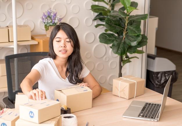 Владелец малого бизнеса, женщина, проверяющая заказ на покупку в ноутбуке и пишущая о доставке на коробке упаковки - концепция продажи онлайн или онлайн-покупок
