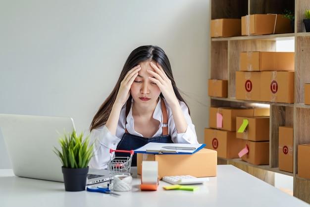 소기업 소유자는 온라인 판매 소포 상자와 책상 위에 놓인 노트북으로 작업하는 것이 지겹습니다.