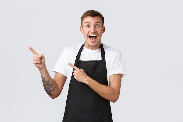 Кафе владельцев малого бизнеса и концепция персонала взволновали счастливого красивого белокурого парня-бариста в кафе ...