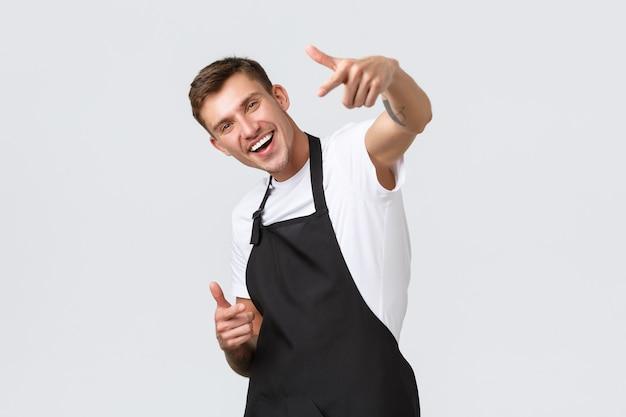 소기업 소유자, 커피숍 및 직원 개념. 친절하고 잘 생긴 바리스타가 춤을 추고 카메라를 가리키며 카페에서 음료를 즐기도록 초대하고, 행복하게 웃고, 손님을 선택합니다.