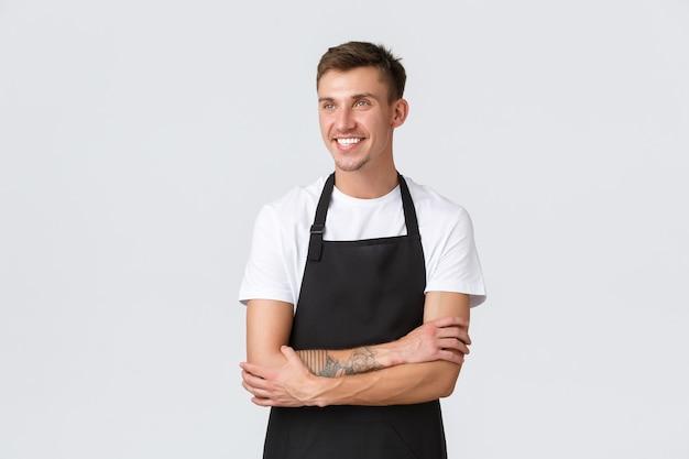 소기업 소유자, 커피숍 및 직원 개념. 잘생긴 쾌활한 금발 남자 바리스타, 앞치마를 입고 만족스러운 미소로 만족스러운 왼쪽 상단 모서리에 기뻐 보이는 아르바이트