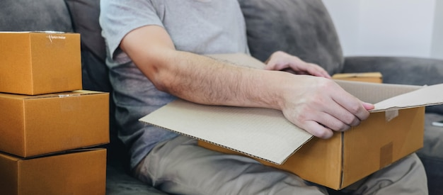 Small business parcel for shipping, happy man opening online shopping package box with parcel while sitting on sofa at home.