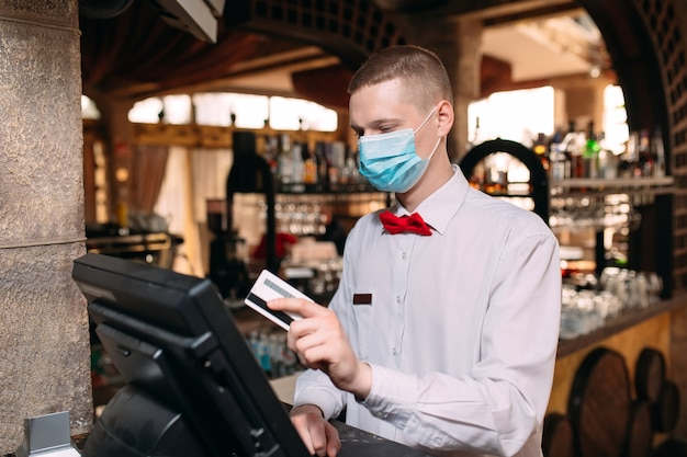 Small business, people and service concept. man or waiter in medical mask at counter with cashbox working at bar or coffee shop.