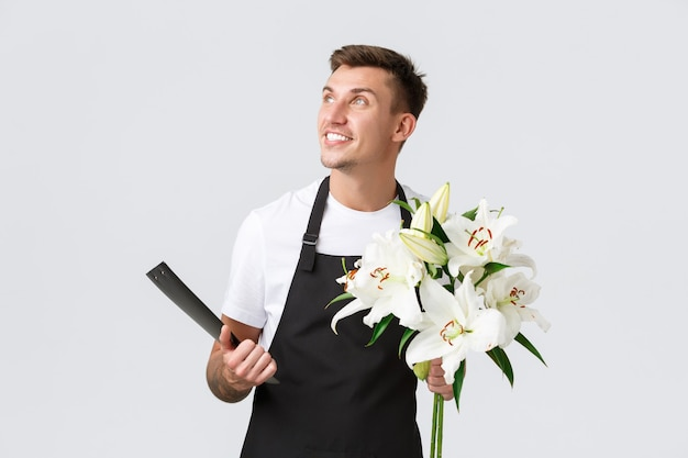 Small business retail and employees concept handsome salesman delivery guy from flower shop holding ...
