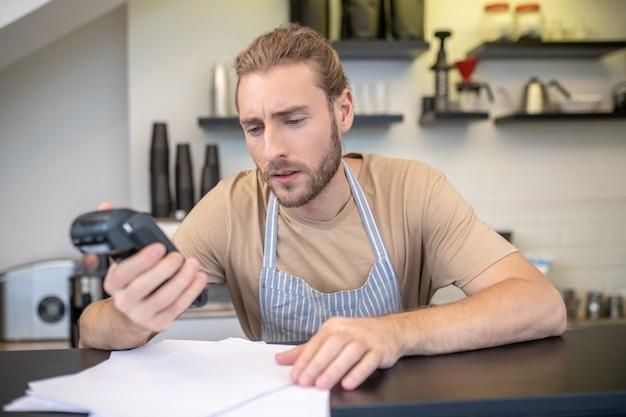 Малый бизнес. умный молодой бородатый сосредоточенный мужчина в фартуке, подсчитывающий прибыли и расходы своего кафе