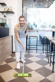 중소기업. 하루 동안 그의 카페에서 앞치마 청소 바닥에 웃는 젊은 성인 남자