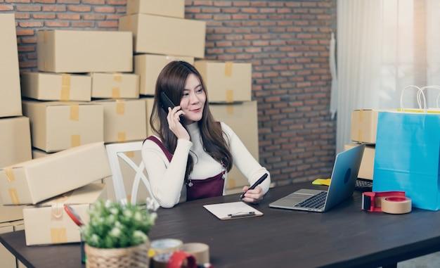 中小企業のスタートアップ起業家smeまたは自宅やオフィスでボックスを扱うフリーランスの女性。配送パッケージの取り扱い