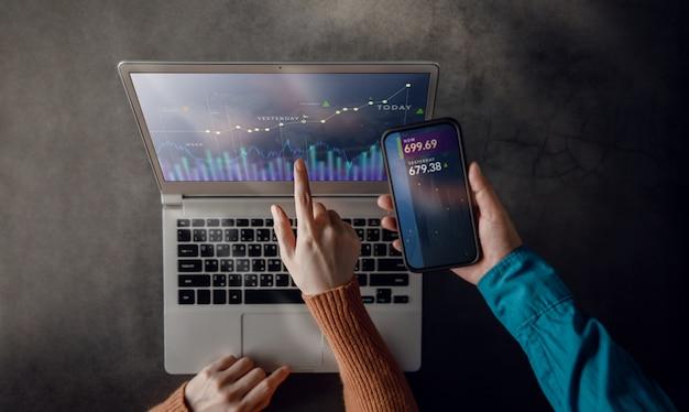 ラップトップで一緒に働く中小企業のチームワーク。コンピューター画面に株式市場データ分析を表示