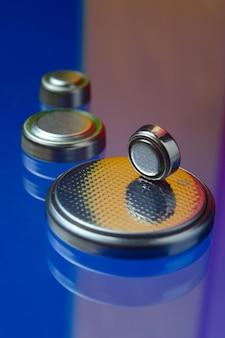 Маленькие кнопочные батарейки разного размера, выделенные красным и оранжевым цветом, лежат на синем фоне. крупный план.