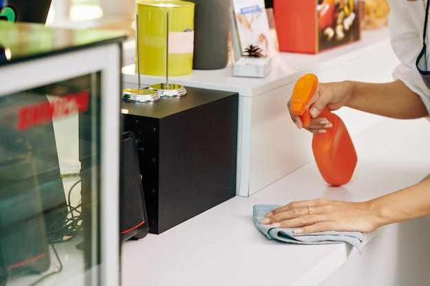 小さなカフェのオーナーがカウンターの表面に消毒用洗剤をスプレーし、柔らかい布で拭きます