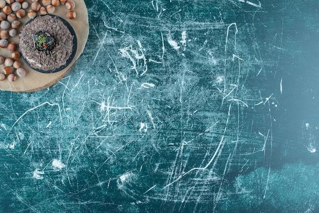 Una piccola torta e un mazzetto di nocciole su una tavola sull'azzurro.