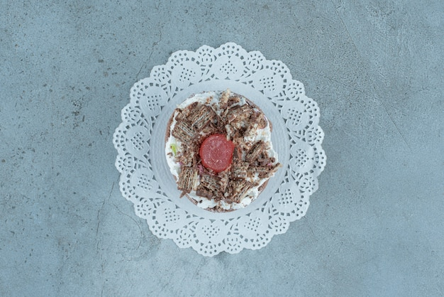 Una piccola torta su un centrino su fondo di marmo. foto di alta qualità