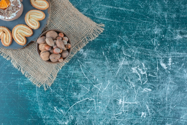 A small cake and flaky cookies on a board next to a bowl of hazelnuts on blue background. high quality photo