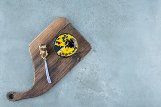 Una piccola torta e una forchetta su una tavola di legno su fondo di marmo. foto di alta qualità